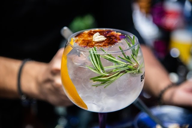 Glass filled with vodka garnished with orange peel and a sprig of herb