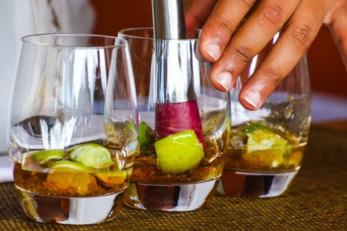 Muddling ingredients for a cocktail drink