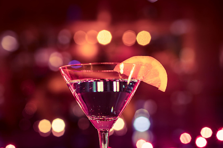 Close up of a single martini against fairy lights