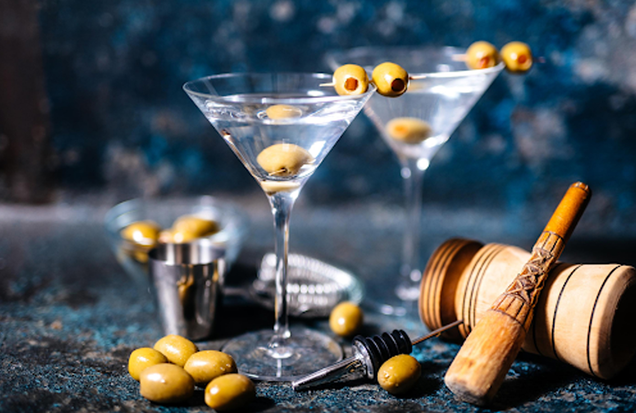 Martinis with olives against a blue background