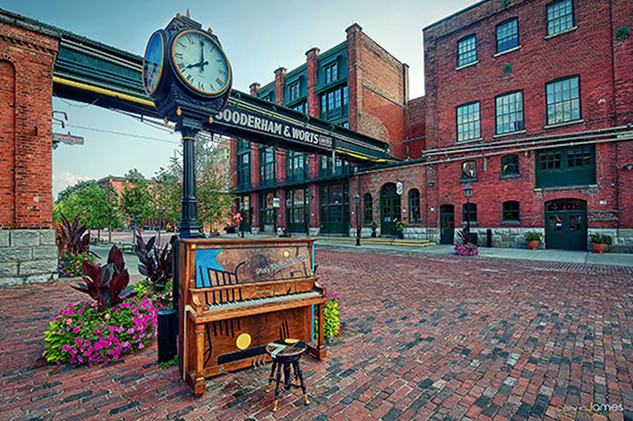 The Distillery Historic District Clock with a piano beside it