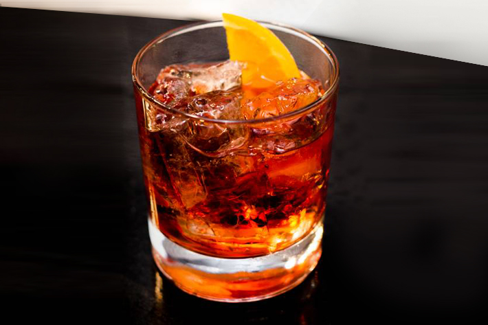 A Negroni served with ice and a lemon slice