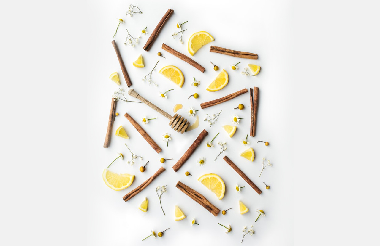 A flat lay shot of cinnamon sticks, daisies, lemon slices, and a honey mixer bar spoon