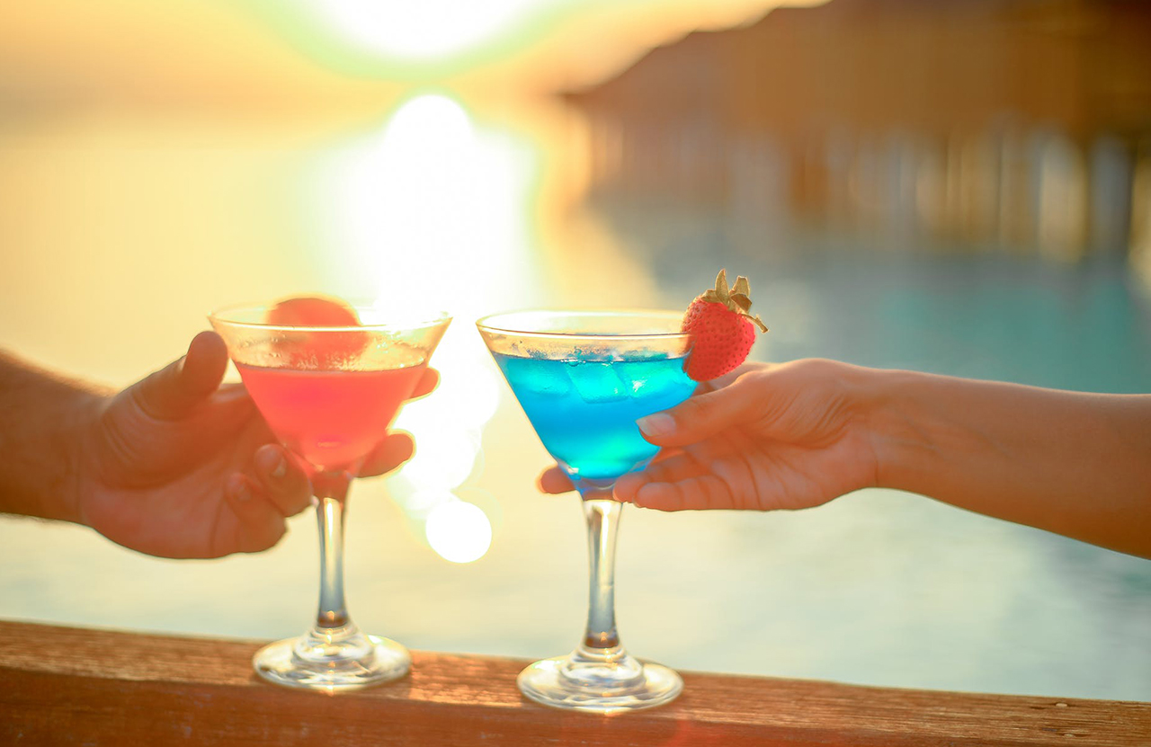 Two people toasting martinis by the sunset