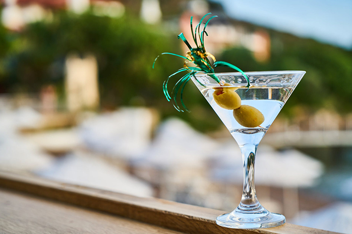 A martini with a lemon twist by the poolside