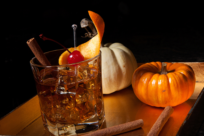 An old fashioned made with whisky and decorative pumpkins