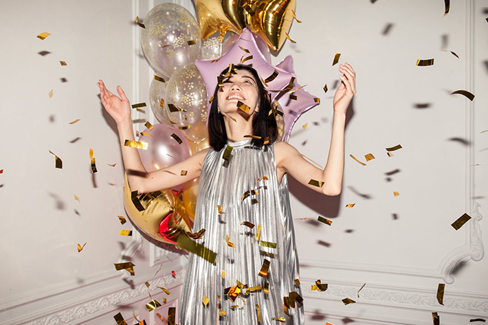 A woman looking a gold confetti and balloons