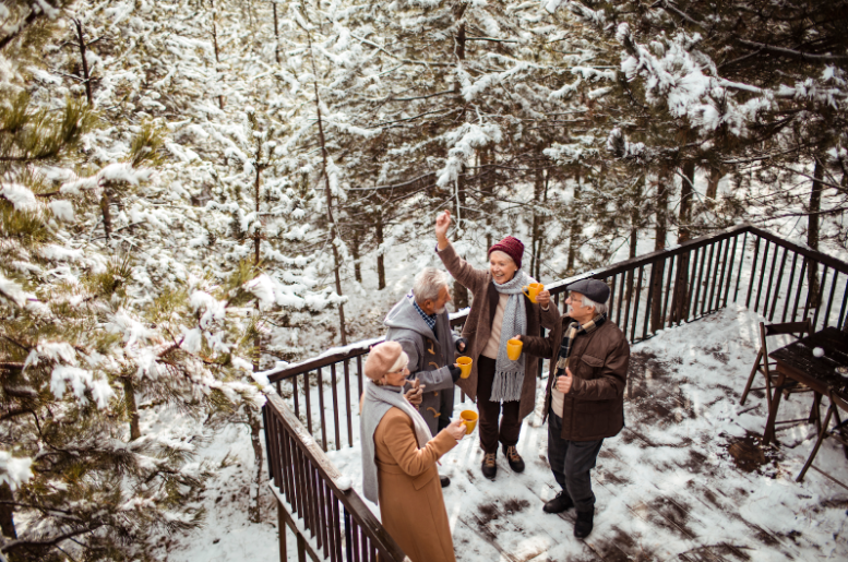 A family enjoys hot cocktails on their deck surrounded by snowy trees
