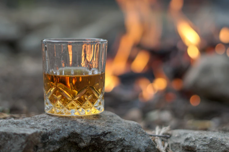 A glass of whisky by a campfire