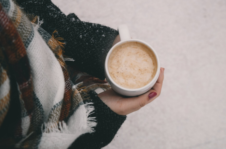 A woman holding a hot drink outdoors in the snow