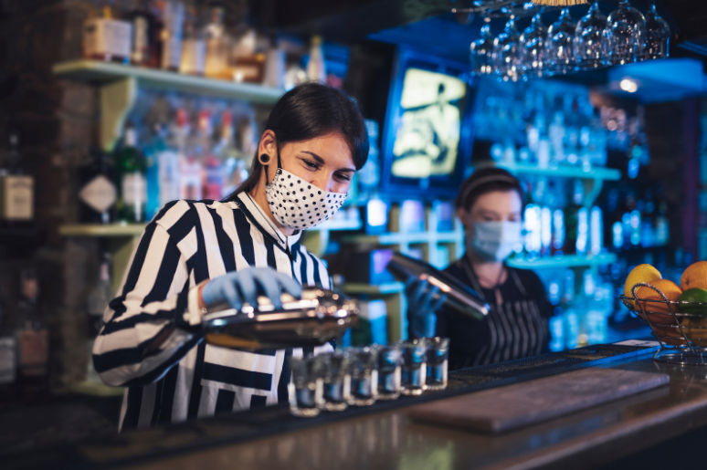 A masked bartender pours shots of rum