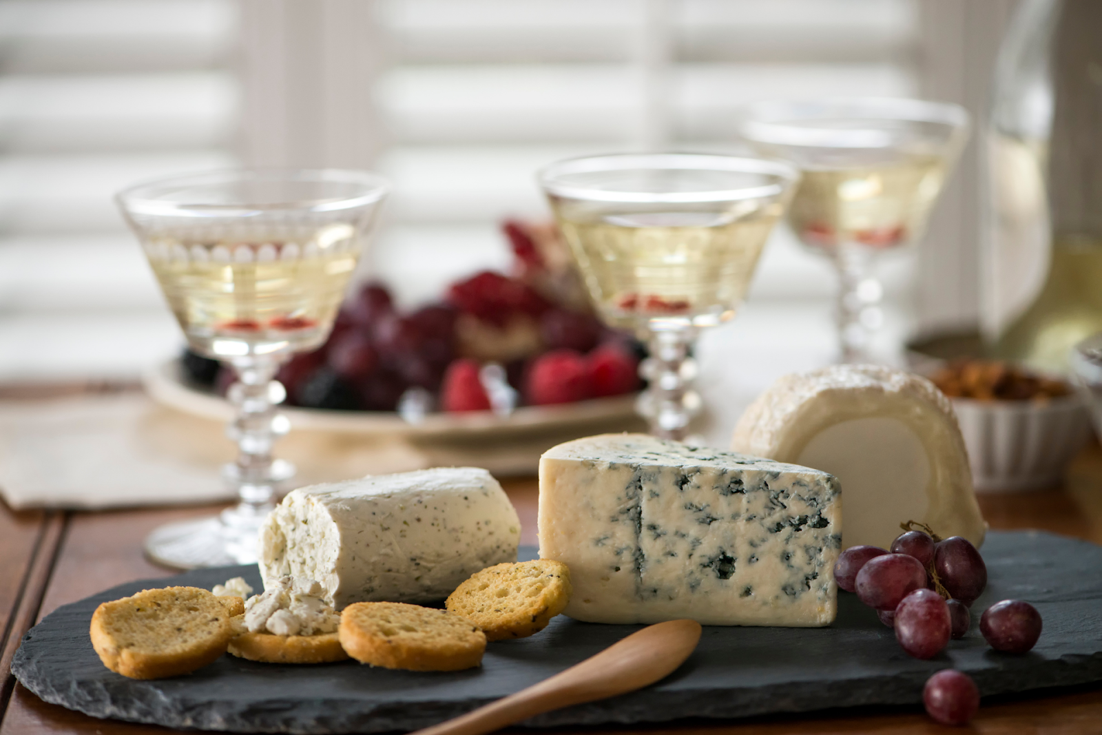 A cheese board with crackers, fruit, and cocktails