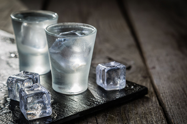 Two glasses of clear liquid and ice cubes on a cutting board